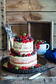 A two-tiered semi-naked cake with fresh berries
