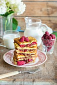 A pile of French toast with hazelnut & chocolate spread and fresh raspberries, served with milk