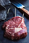 Raw entrecote with a butcher's hook, a knife and a tea towel on a black surface