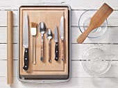 Assorted knives and spoons and a brush on a wooden board, a citrus press, a glass bowl, a spatula and baking paper