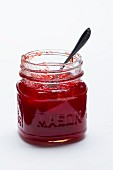 A jar of strawberry jam on a white surface
