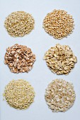 Six piles of various grains on a white surface
