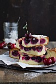 Slices of cherry tray bake cake with icing sugar