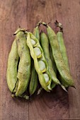 Broad beans in pods on a wooden surface