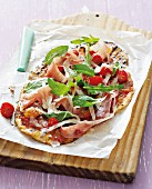 Pan pizza with tomatoes, raw ham, rocket and Parmesan