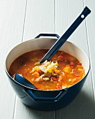 Vegetable soup in a cooking pot with a soup ladle