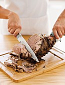 Roasted leg of lamb being carved