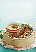 Chicken satay kebabs with hot peanut sauce, served in a steamer basket