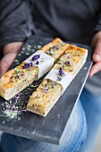 Slices of onion cake with lavender flowers and basil salt