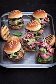 Mini burgers with roast beef, avocado cream, spinach and bean sprouts