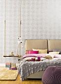Doppelbett mit Betthaupt und Kissen neben rustikaler Schaukel als Nachttisch vor grau gemusterter Tapete