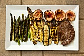 Grilled steak and vegetables on a rectangular plate