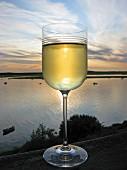 Weissweinglas bei Sonnenuntergang am Fluss