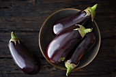 Aubergines in a bowl and next to it