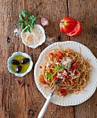 Wholewheat spaghetti with tomato, Parmesan, olives and basil