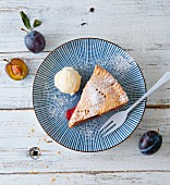 A slice of plum pie on a plate with a scoop of ice cream