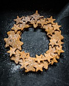 A wreath made of gingerbread stars dusted with icing sugar (seen from above)