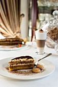 Tiramisu cake with mascarpone mousse, topped with coffee and cocoa powder and served with almond biscotti