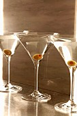 Three Martini cocktails with green olives