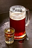 A tankard of beer next to a schnapps glass