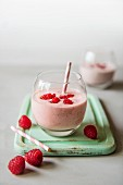 A glass of raspberry drinking yoghurt with fresh raspberries