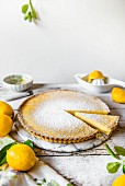 A lemon tart dusted with icing sugar on a marble plate with one slice removed