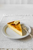 A slice of lemon tart on a plate with a fork