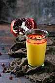 A glass of mango & pomegranate smoothie with pomegranate seeds