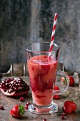 A glass of strawberry & pomegranate smoothie with a straw and fresh berries