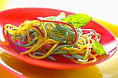 Colourful spaghetti on a red plate