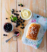 A sweet bun with butter and blackcurrant jam