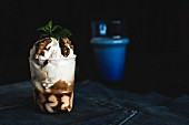 A cake sundae in a glass with walnuts and mint