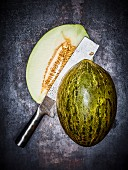 A Santa Claus melon (piel de sapo), cut in half, with a cleaver