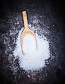 A pile of sugar with a wooden scoop