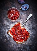 Home-made plum sauce in a glass jar and on bread
