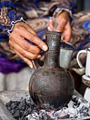 Frau bereitet Kaffee in Jebena (Kaffeekanne aus Ton) zu, traditionelle Kaffeezeremonie in Äthiopien