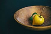 A fresh lemon with a stem in a wooden bowl
