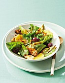Warm summer salad with chicken, avocado, olives and orange