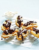 Chocolate eclairs filled with cream on a cooling rack
