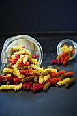 Bunte Fusilli in einem Messbecher und einem Glas, umgekippt