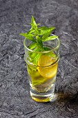 A glass of lemonade with lemon verbena and ice cubes