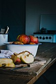 Fresh apples, some sliced, in a rustic kitchen