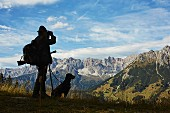A hunter with a hound in a mountain setting