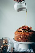 Maple syrup being drizzled in a fig & pear cake with walnuts
