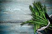 A bunch of green asparagus on a wooden surface