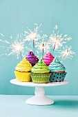 Bunte Cupcakes mit Wunderkerze verziert