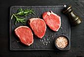 Rohe Rindersteaks (beef eye round steaks) mit Gewürzen und Rosmarin auf schwarzer Schieferplatte
