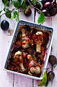 Chicken drumsticks with bacon and plums