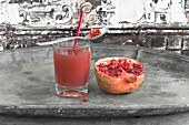 Pomegranate juice in a glass with a straw and spoon next to a pomegranate sliced in half
