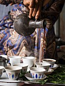 A woman serving coffee from Jabena during a traditional coffee ceremony in Ethiopia